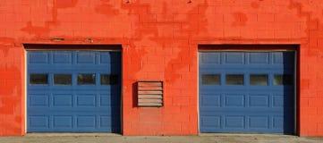 Portas alaranjadas e azuis da garagem foto de stock