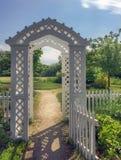 Portas de jardim de madeira brancas do mandril de Nova Inglaterra e trajeto ensolarado fotografia de stock royalty free