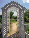 Portas de jardim de madeira brancas do mandril de Nova Inglaterra e trajeto ensolarado fotos de stock