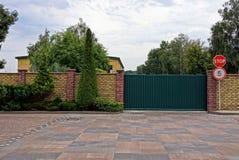 Portas do ferro e sinais de estrada verdes perto de uma parede de tijolo com plantas decorativas Fotos de Stock