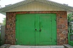 Portas verdes do ferro e uma porta com cadeado em uma construção de pedra Fotos de Stock