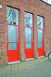 Portas vermelhas na parede de tijolo, indústria da construção civil, Fotografia de Stock