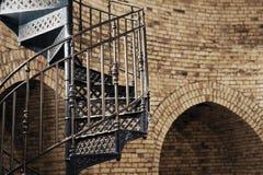Portata della scala a chiocciola del metallo nel retro stile sui precedenti di vecchia parete di pietra con gli arché fotografie stock
