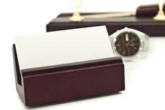 Portatarjetas con la tarjeta de visita en blanco, reloj Foto de archivo libre de regalías