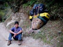 Portatore nepalese lungo la strada alla parte superiore Immagini Stock Libere da Diritti