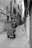 Portatore a Venezia con i pacchetti di consegna su un carretto Immagini Stock