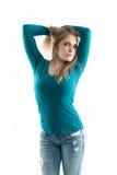 Porte à côté de fille dans des jeans retenant le cheveu et regardant f Images stock