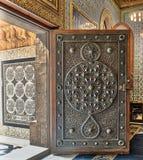 Porte âgée en bois ouverte avec les modèles floraux bronzés fleuris, mosquée du palais de Manial de prince Mohammed Ali, le Caire Photographie stock libre de droits