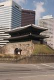Porte antique de ville et constructions modernes Photographie stock libre de droits