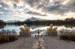 Porte avec des sculptures à un lac pendant le coucher du soleil Image stock