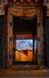 Porte avec la vue des montagnes au monastère de Drak Yerpa près de Lhasa, Thibet Photos libres de droits
