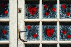 Porte blanche âgée avec des symboles rouges de coeur Photos stock