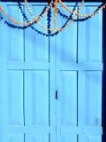 Porte bleue avec les fleurs accrochantes du Dharma Photographie stock