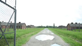 Porte d'entrée et la barrière électrique du camp de concentration avec des casernes banque de vidéos