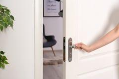 Porte d'ouverture de jeune femme à la pièce admirablement disposée photographie stock