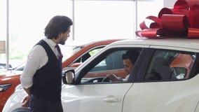 Porte d'ouverture professionnelle de vendeur de voiture d'une voiture pour son client masculin photos libres de droits