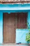 Porte de Brown et fenêtre râpée sur le mur bleu Image stock