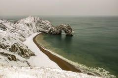 Porte de Durdle couverte dans la neige un matin d'hiver Images libres de droits