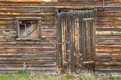 Porte de voie de garage affligée de grange avec la fenêtre encombrée Image stock