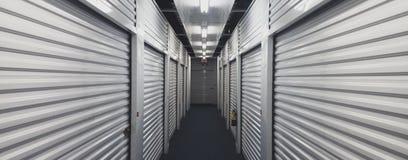 Porte dell'unità di stoccaggio di auto da ogni lato di un corridoio dell'interno immagine stock