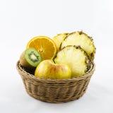 Porte des fruits la composition dans le panier en osier avec les fruits coupés Images libres de droits