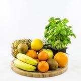 Porte des fruits la composition sur le conseil en bois avec le basilic Images stock