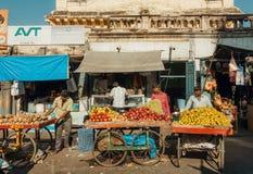 Porte des fruits les marchands ambulants commerçant des pommes, des oranges et des mandarines sur le marché occupé Images stock