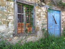Porte di legno blu sulla vecchia Camera greca di pietra del villaggio fotografia stock