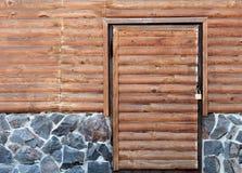 Porte en bois à la lingerie d'une maison se tenant sur une base en pierre Photos libres de droits