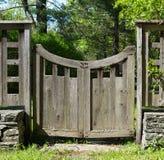 Porte en bois affligée avec la pierre, l'herbe et les arbres empilés Images stock