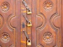 Porte en bois antique fermée avec trois cadenas Image stock