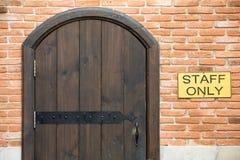 Porte en bois arquée sur le mur de briques Photographie stock
