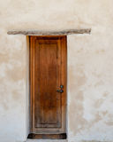 Porte en bois contre le mur de plâtre lavé par blanc Photographie stock