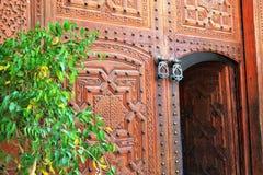 Porte en bois décorative marocaine traditionnelle et heurtoirs en bronze image stock