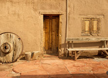 Porte en bois d'encart dans un mur d'adobe avec le passage couvert de brique rouge images stock
