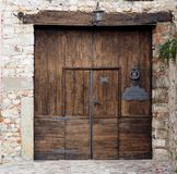 Porte en bois d'entrée dans le style médiéval sur le mur en pierre avec des travaux de fer travaillé et une lanterne sur le faisc Image libre de droits
