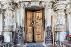 Porte en bois dans le temple hindou historique avec les murs en pierre, les collumns, les découpages et les sculptures, Inde photographie stock