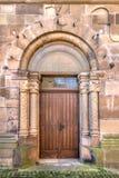 Porte en bois dans un portail fait un pas roman Photo stock