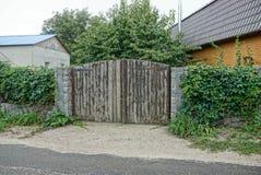 Porte en bois grise et une barrière envahie avec des barrières près de la route goudronnée photographie stock