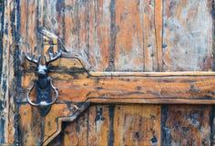 Porte en bois grunge avec le heurtoir de porte en métal de tête de renne Image libre de droits
