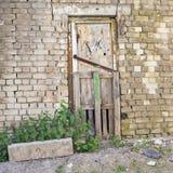 Porte en bois grunge, fond criqué de mur de briques Photos libres de droits