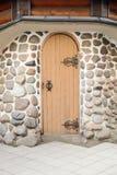 Porte en bois médiévale arquée dans un mur en pierre Images stock