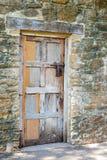 Porte en bois multicolore contre le mur en pierre usé Photo libre de droits