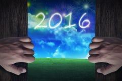 Porte en bois ouverte de main à la ville qui célèbrent la nouvelle année 2016 Photographie stock libre de droits