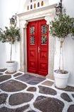 Porte en bois rouge décorée des palmiers dans Mykonos, Grèce Photos libres de droits