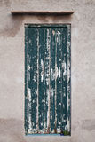 Porte en bois verte sale dans le vieux mur en pierre Photo libre de droits