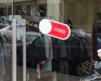 Porte en verre d'un magasin d'habillement avec un signe fermé photographie stock