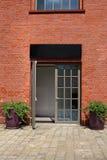 Porte en verre dans le mur de briques avec deux pots de fleurs Photographie stock