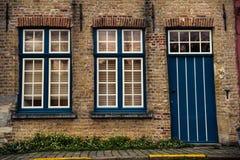 Porte et fenêtres en bois bleues sur le mur de briques de la maison à Bruges, Belgique Photos stock