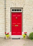 Porte et fleurs rouges Images stock